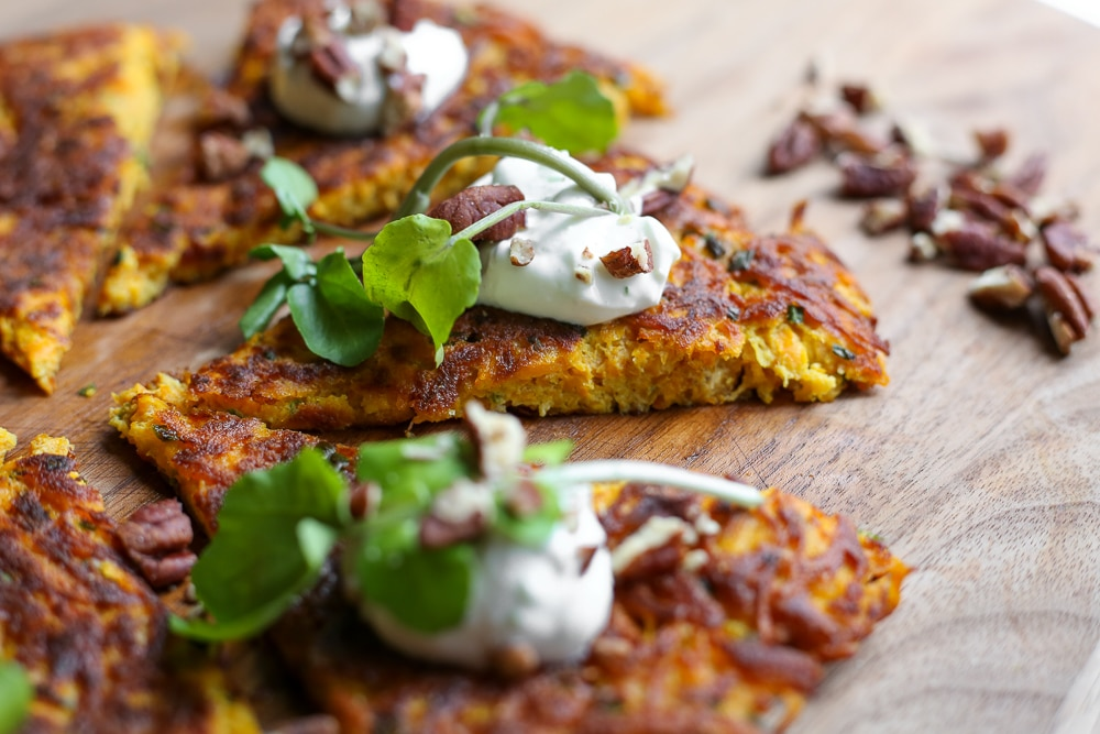 Single angle shot of the butternut Squash Latke cake with lime yogurt on a serving board.