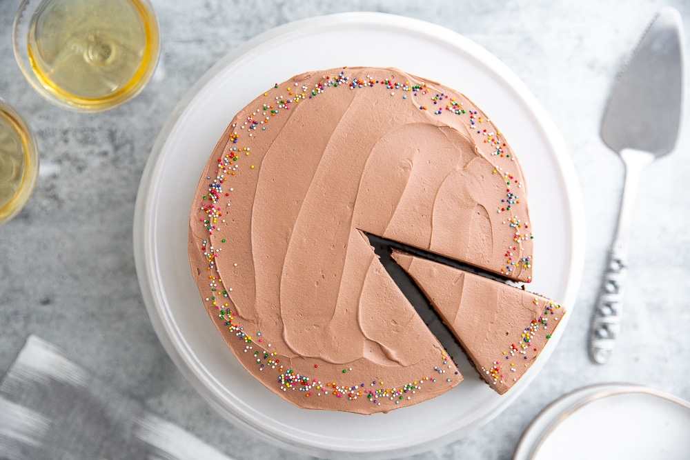 Chocolate quinoa cake with cocoa whipped cream frosting on a cake plate.