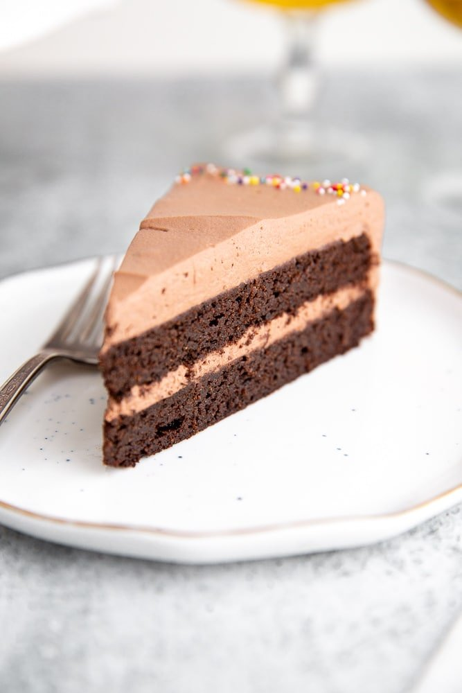 Close up of a slice of chocolate quinoa cake on a plate with a fork.