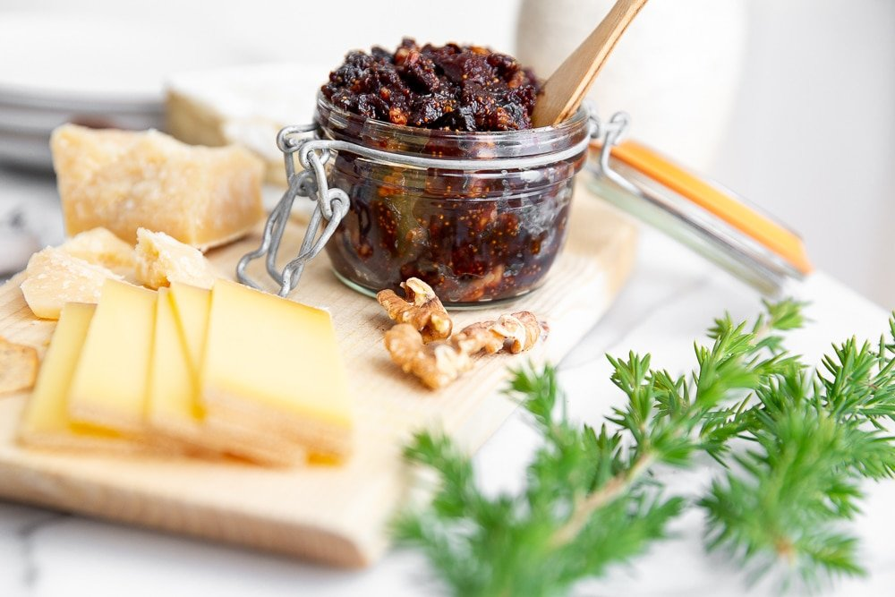 Fig chutney in a jar with a spoon, alongside cheeses and walnuts.