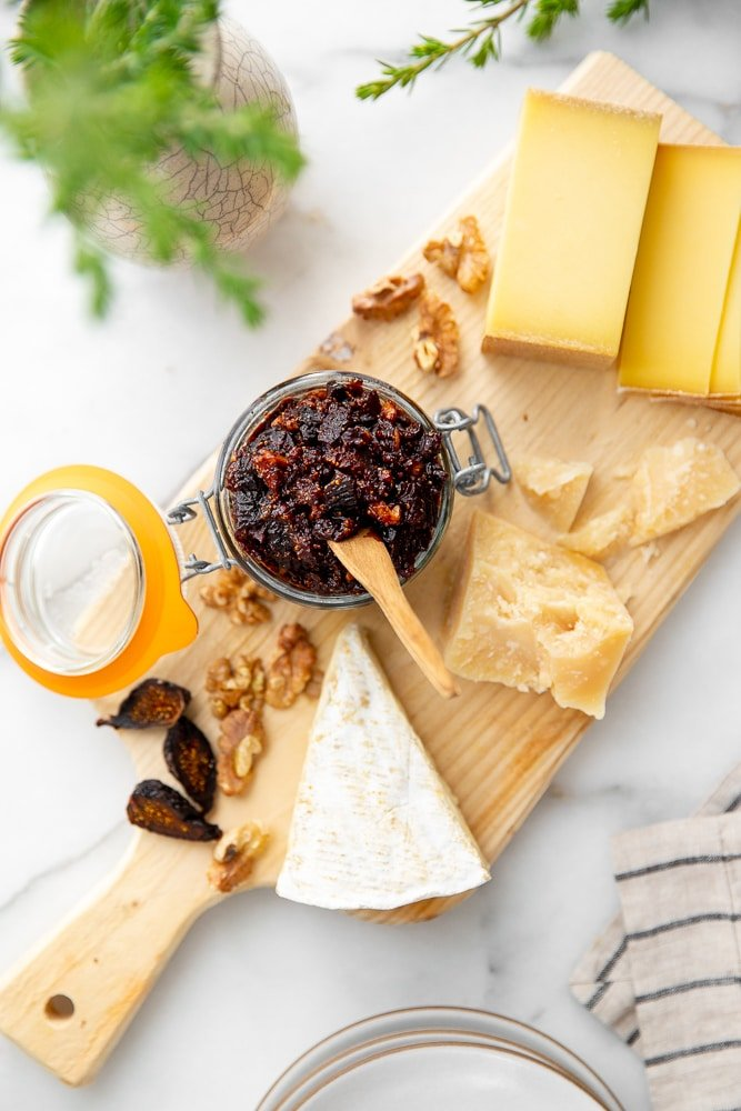 Overhead shot of a serving board with several cheeses and a jar of fig chutney.