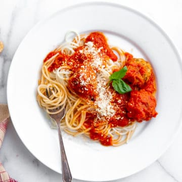 Plate of spaghetti topped with healthy baked turkey meatballs.