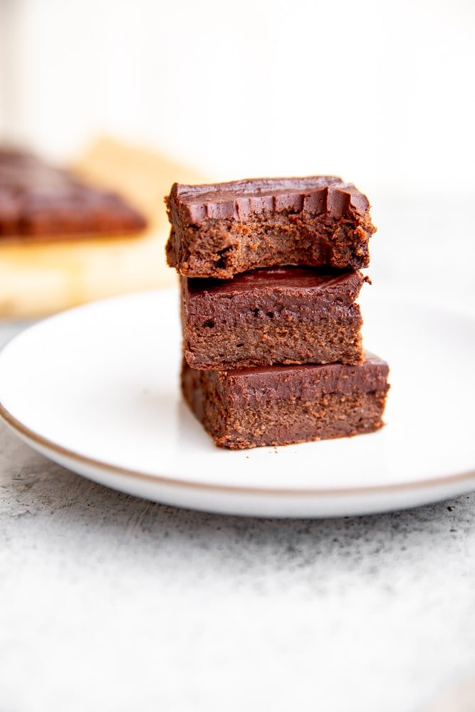Close up of black bean brownies with cacao frosting stacked on a plate.