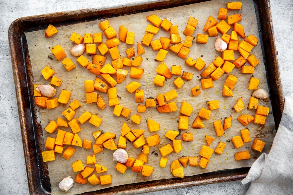 Process shot showing roasted butternut squash cubes on a baking sheet.