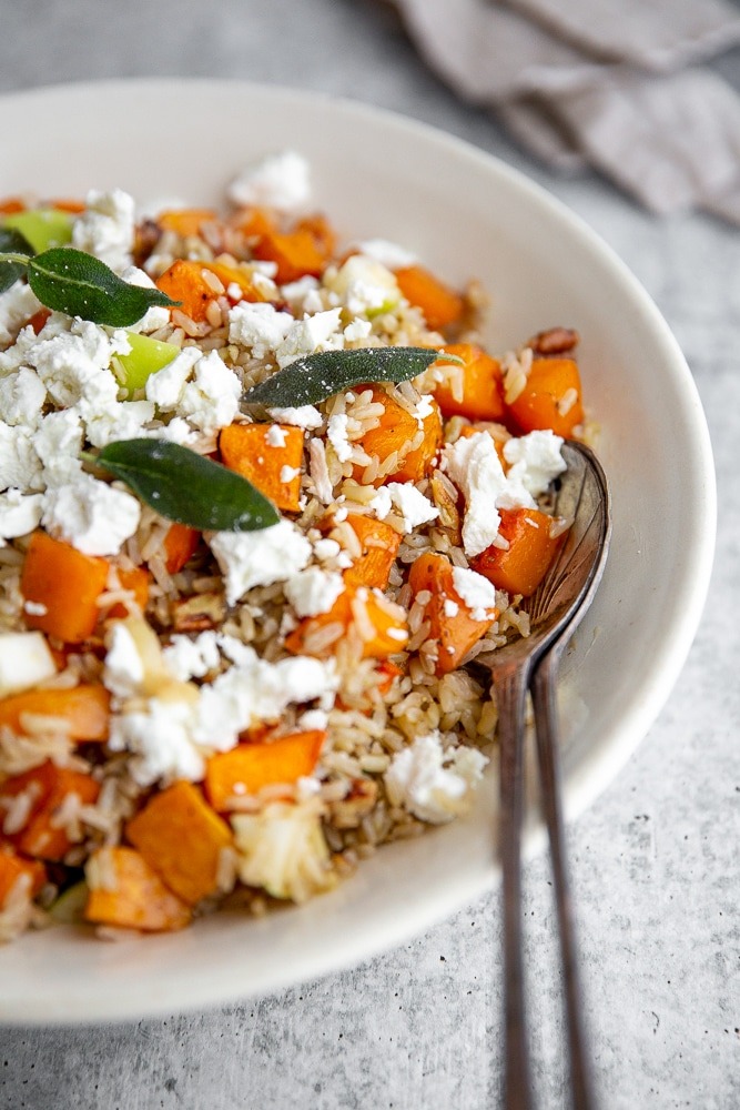 Close-up of roasted butternut squash salad with fried sage leaves on top.