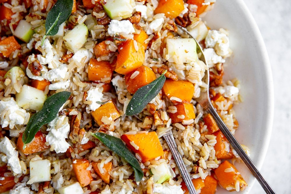 Overhead close-up shot of roasted butternut squash salad with grains, apples and goat cheese.