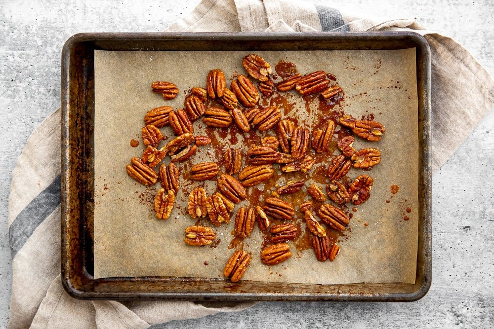 Maple roasted pecans on a baking sheet.