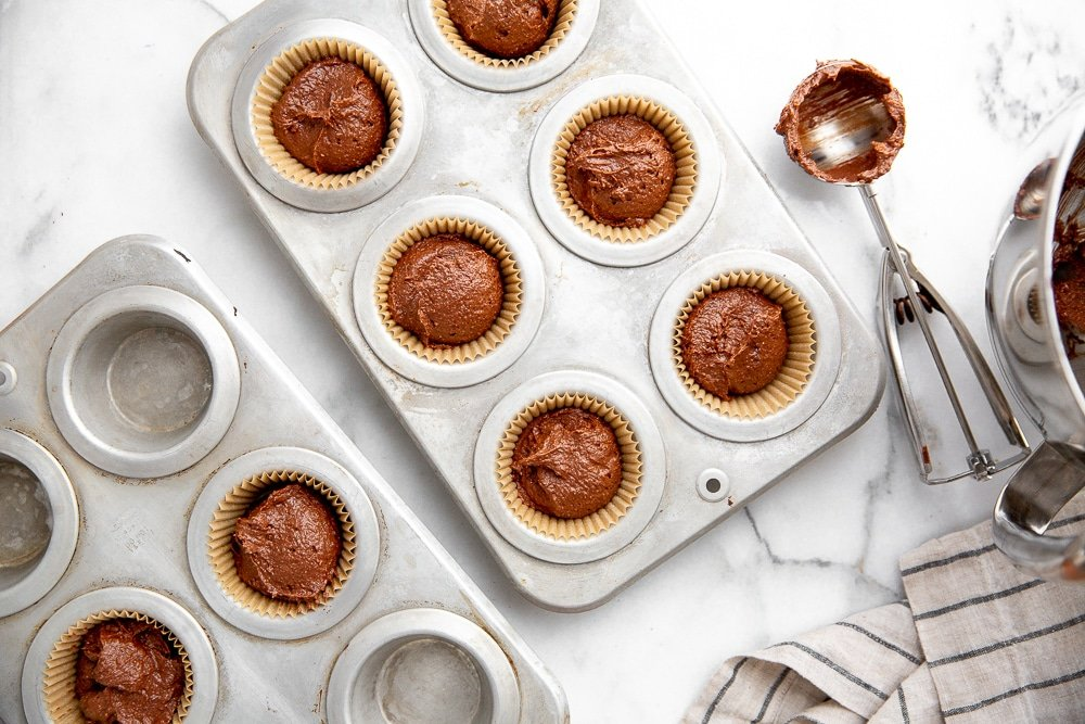 Chocolate cake batter in muffin tins with an ice cream scoop (for scooping the batter) alongside.