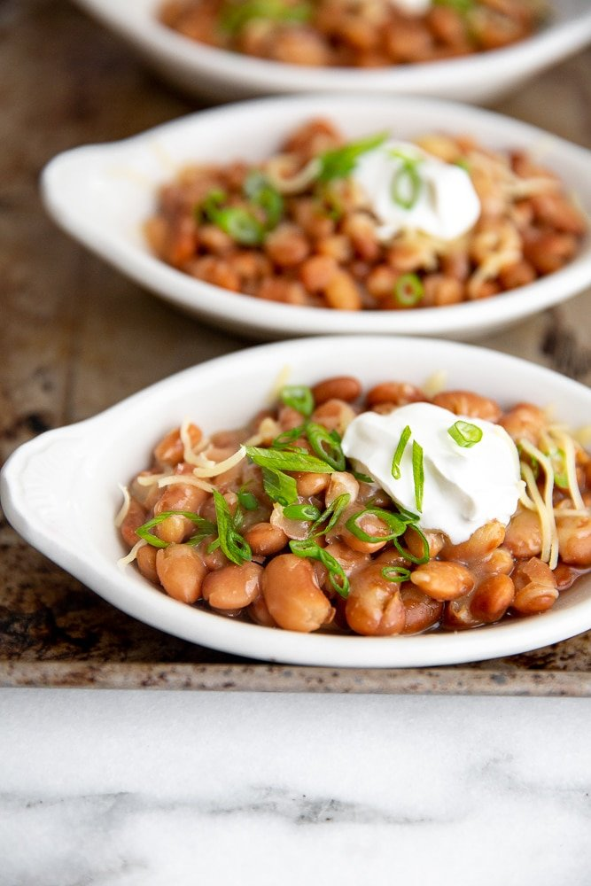 Close up of a dish of pinto beans topped with cheese, sour cream and scallions.