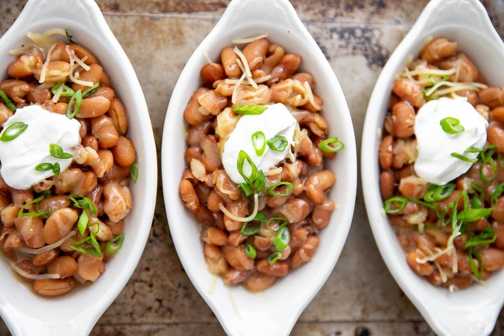 Three serving dishes of Instant Pot pinto beans topped with cheese and sour cream.