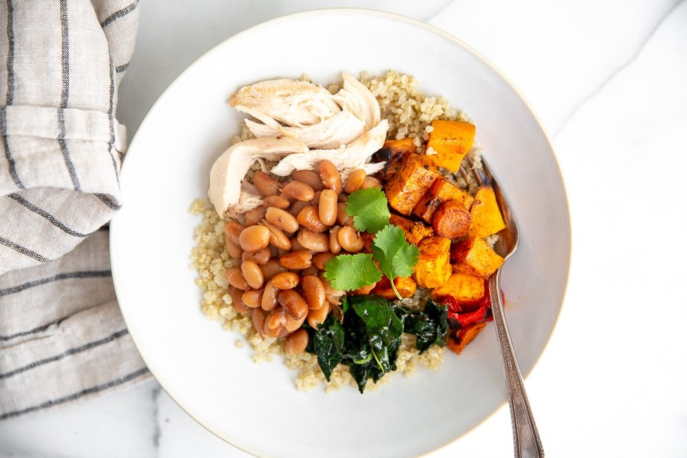 Overhead shot of a grain bowl with vegetables, chicken and pinto beans.