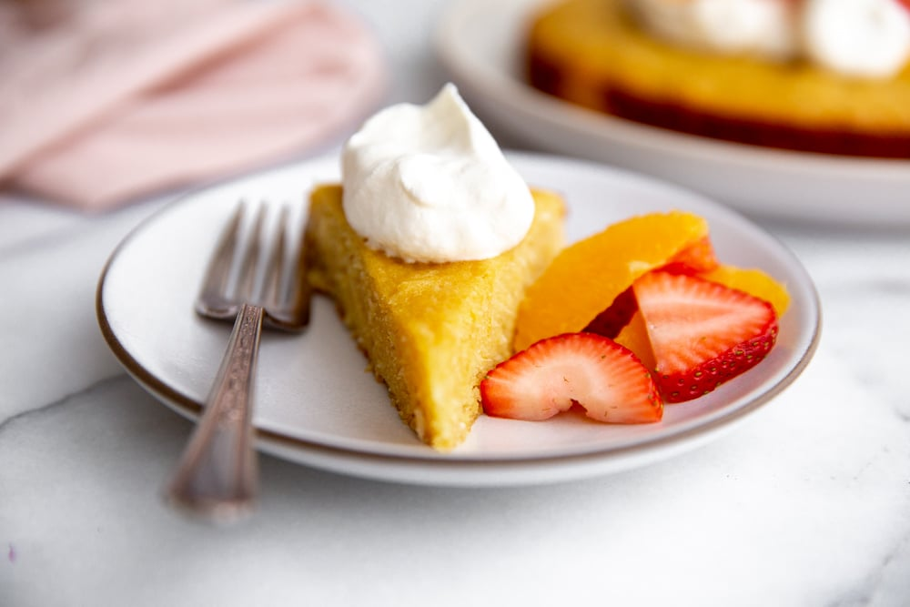 Close up of a slice of almond cake on a plate topped with whipped cream and fruit alongside.