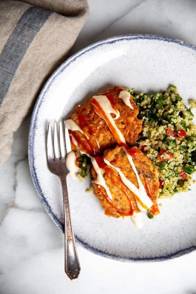 Paleo salmon cakes drizzled with spicy mayo, on a plate over tabbouleh.