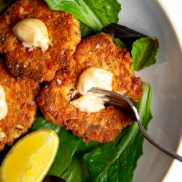 Paleo salmon cakes on a bed of salad greens.