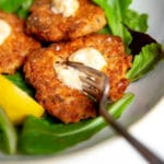 Close up side-view of salmon cakes with spicy mayo, over salad greens.