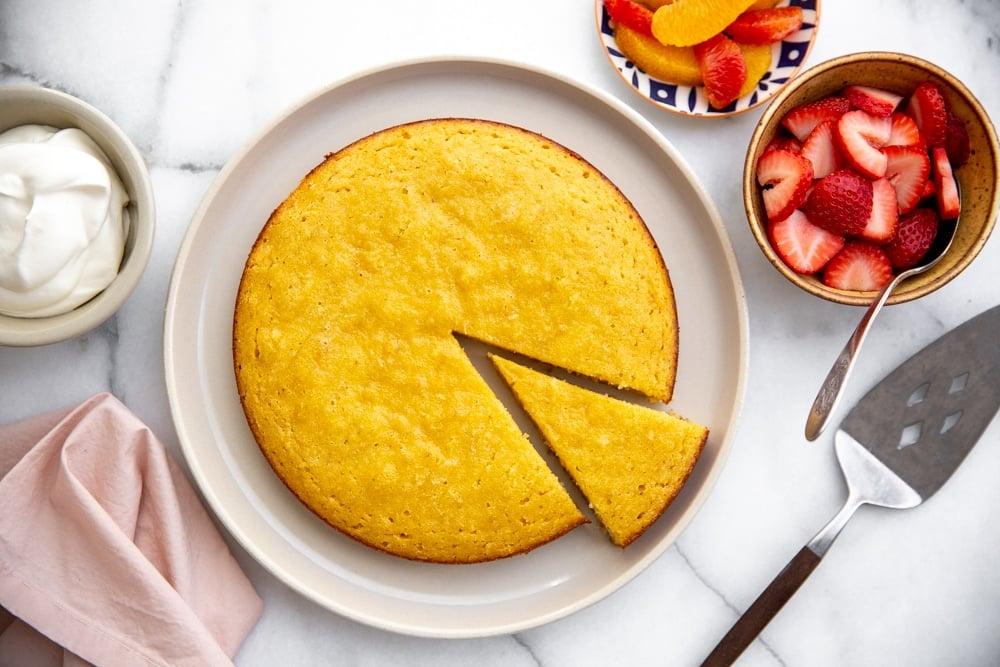 Almond cake on a plate with fruit alongside.