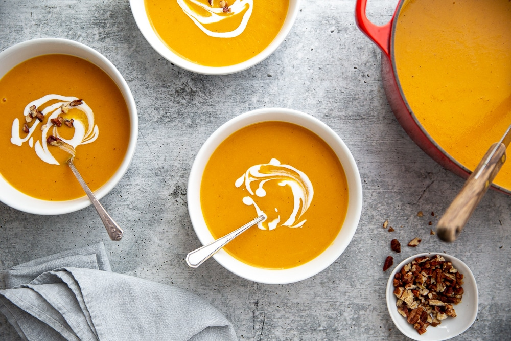 Sweet potato soup in a pot with bowls alongside.