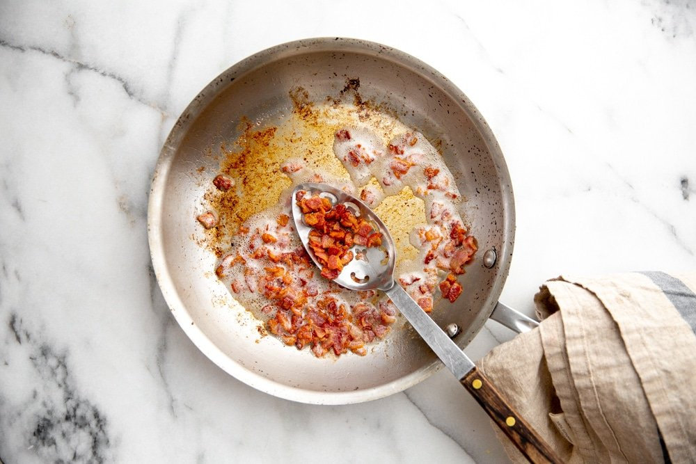 Process shot showing crispy bacon in a skillet.