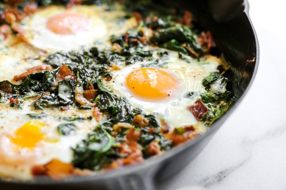 Close-up side view of the spinach baked eggs in a cast iron skillet.