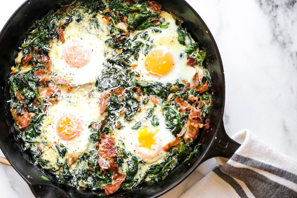 Overhead shot of spinach baked eggs in a cast iron skillet.