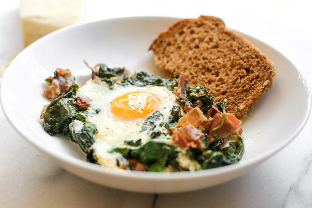 Spinach and egg bake in a serving bowl with a piece of bread alongside.