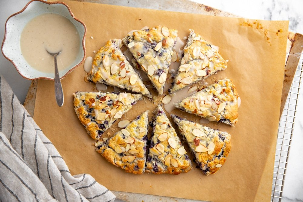 Gluten free blueberry almond scones on a baking sheet with a bowl of lemon glaze alongside.