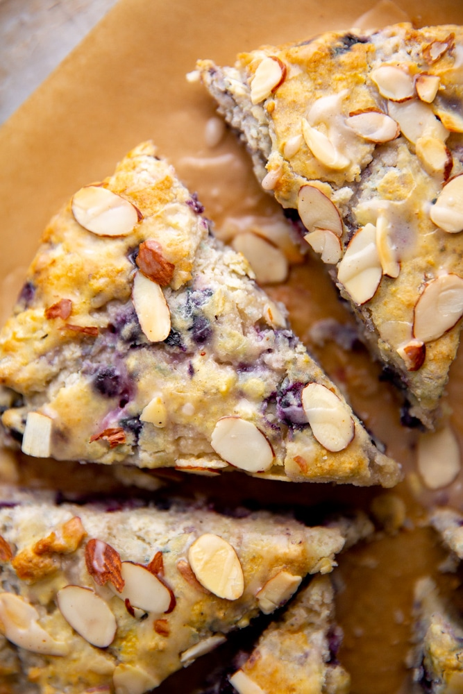 Close up of gluten free blueberry almond scones drizzled with lemon glaze.