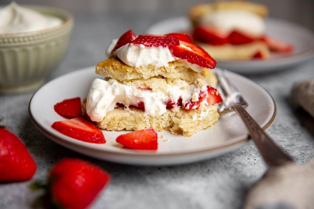 Close up of a half-eaten gluten free strawberry shortcake on a plate.