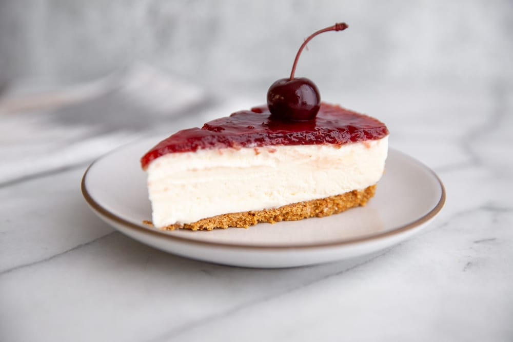 Close-up of a slice of mascarpone cheesecake on a plate.