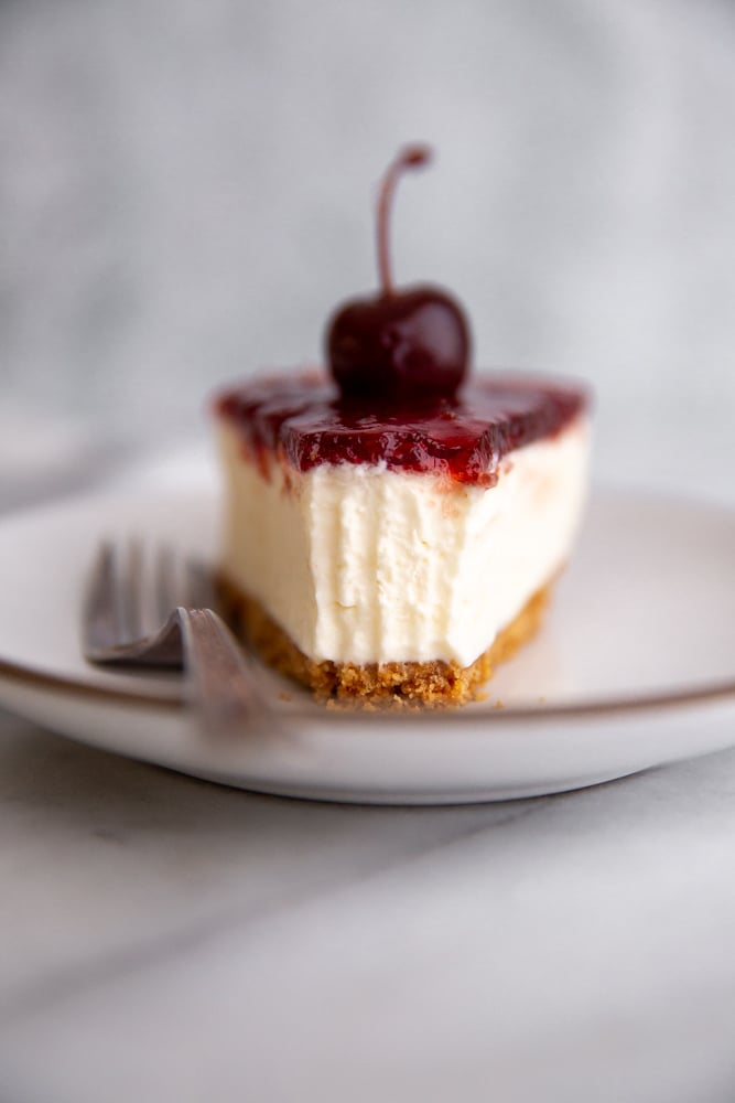 Close-up of a slice of mascarpone cheesecake on a plate with a bite taken out.