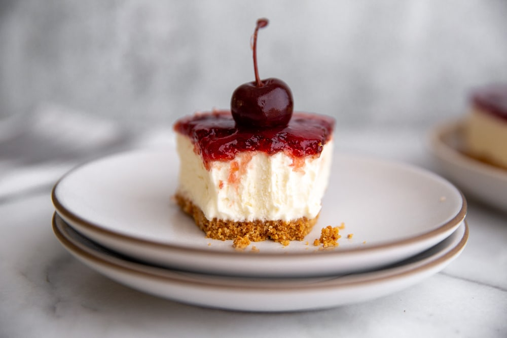 Close up of a slice of cheesecake with a bite taken out.