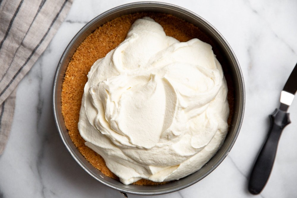 Mascarpone and whipped cream filling in a biscotti crust with an off-set spatula alongside.