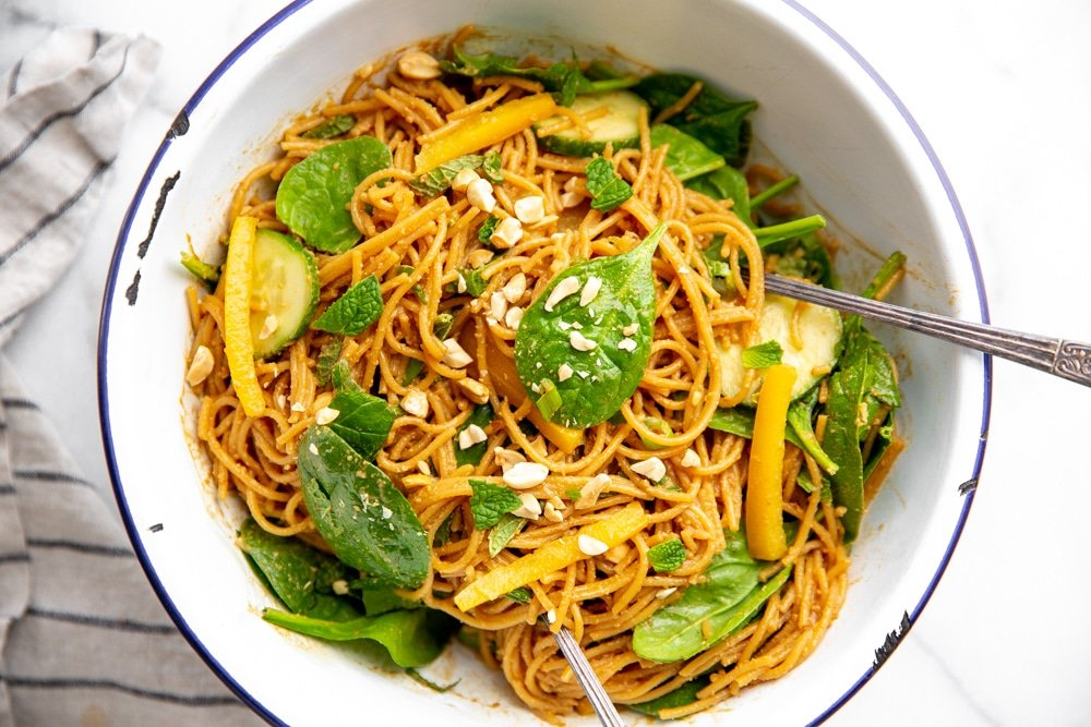 Bowl of cold peanut noodle salad with spinach, cucumbers and peppers.