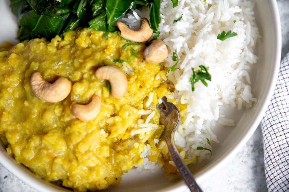 Close up of a fork taking a bite of dahl and rice.