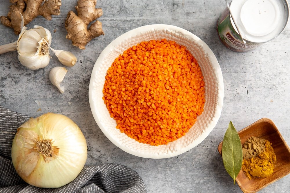 The ingredients for the red lentil dal on a countertop, including red lentils, an onion, coconut milk, garlic, ginger and spices.