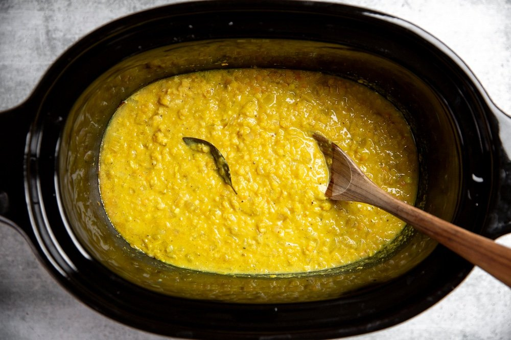 Red lentil dal in a slow cooker with a wooden spoon.