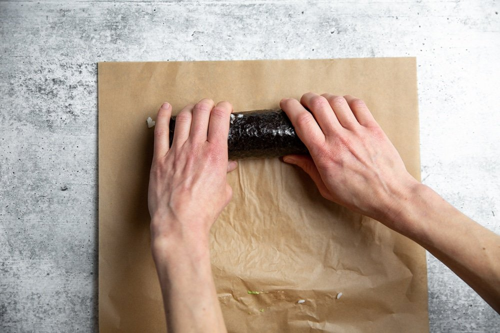 Hands rolling a spicy salmon sushi roll.