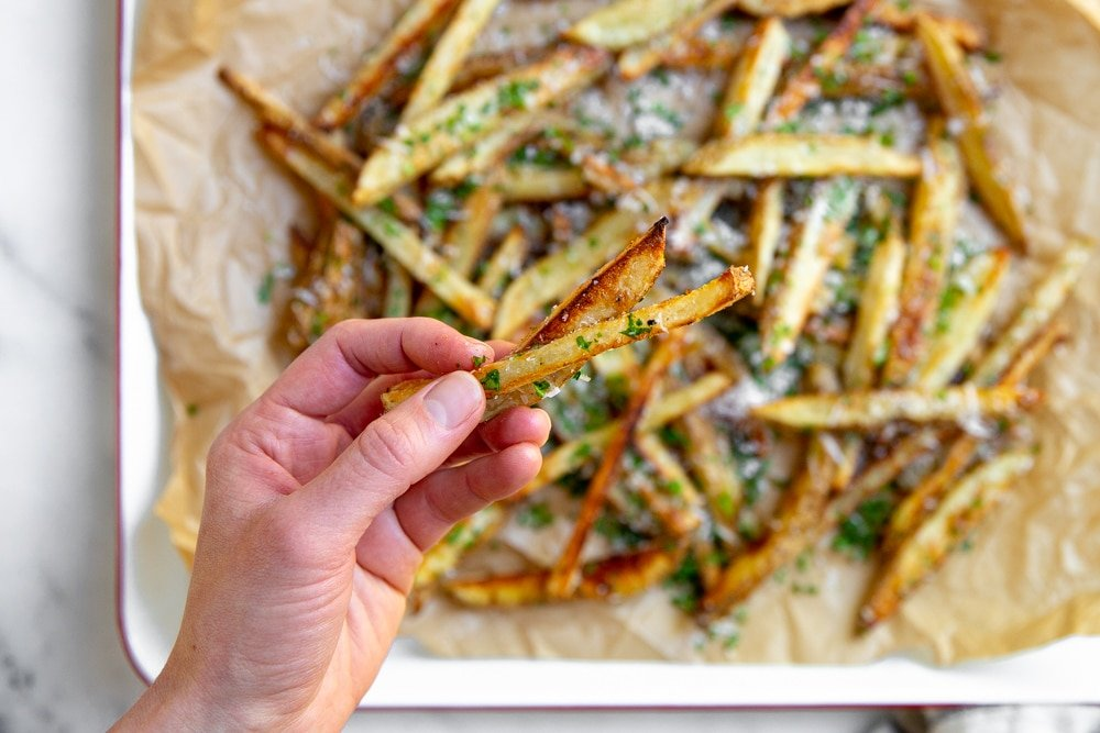 Close up of a hand holding two crispy baked oven fries.