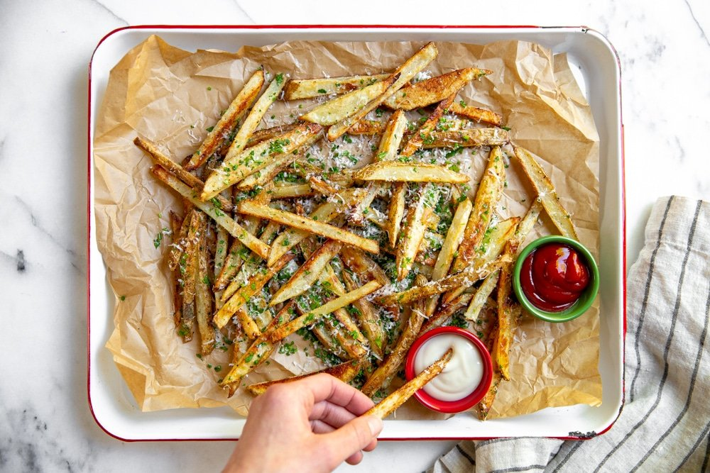 Platter of baked French fries with a hand dipping a fry in aioli.