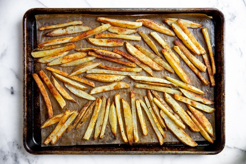 Process shot showing crispy baked oven fries on a baking sheet.