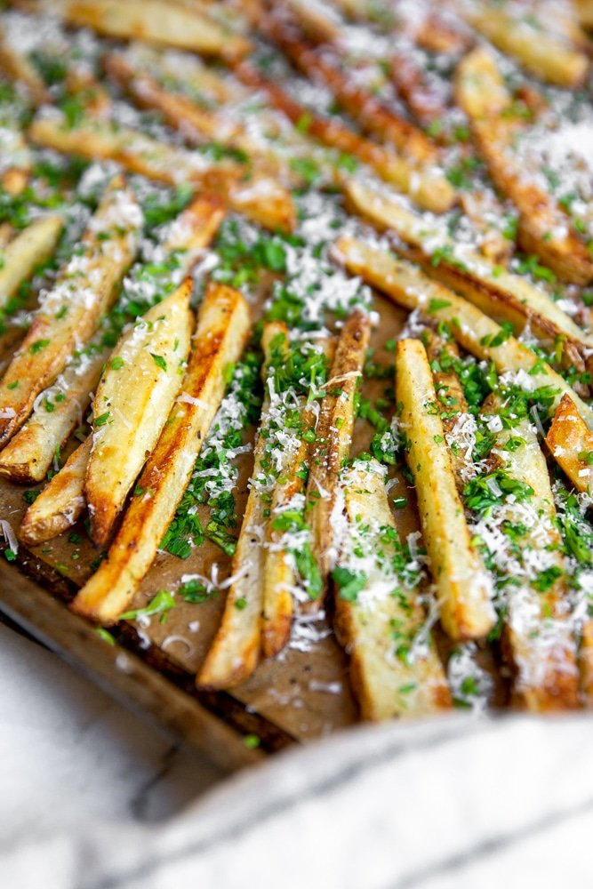 Close up of oven fries on a baking sheet sprinkled with herbs and parmesan.