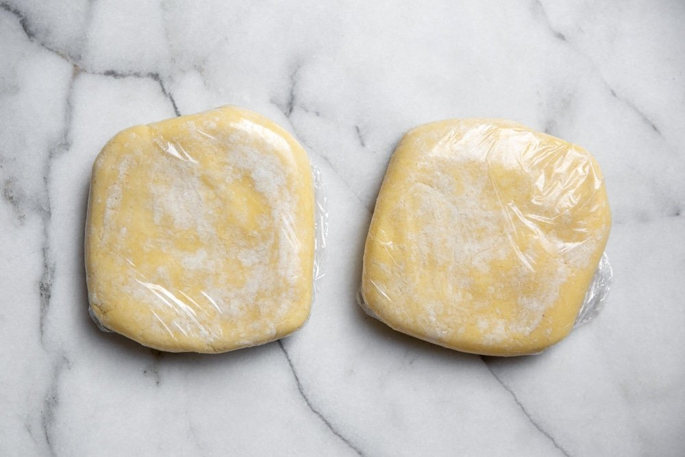 Pie dough disks wrapped in plastic wrap.
