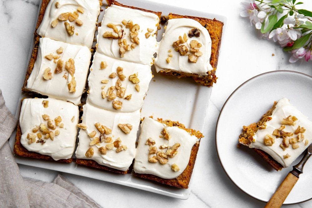 Healthy gluten free carrot cake cut into squares on a platter, with a serving plate alongside.