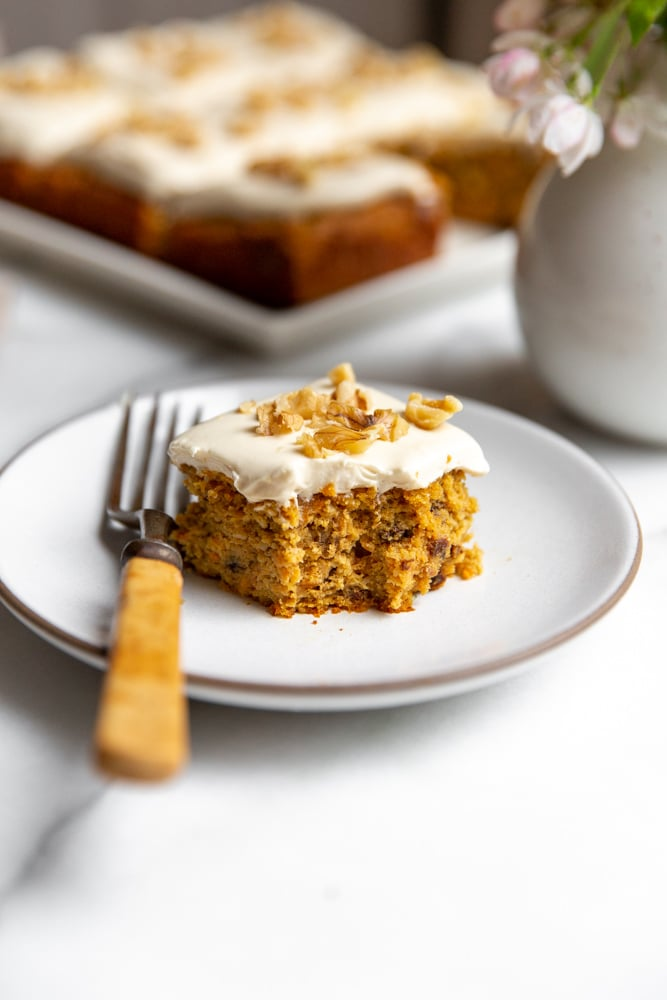 Close up of the carrot cake on a plate with a fork, with a bite taken out.