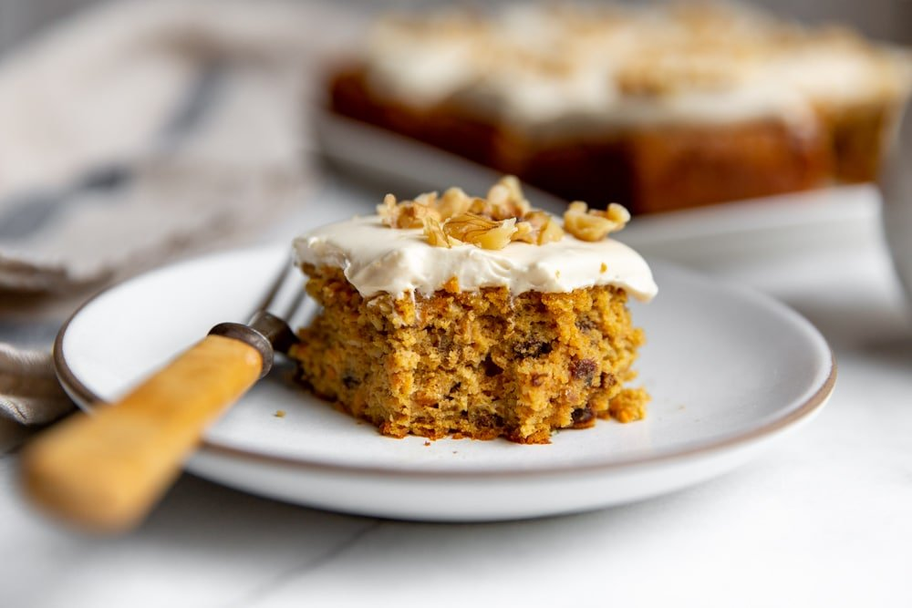 Slice of gluten free carrot cake on a plate with a fork.