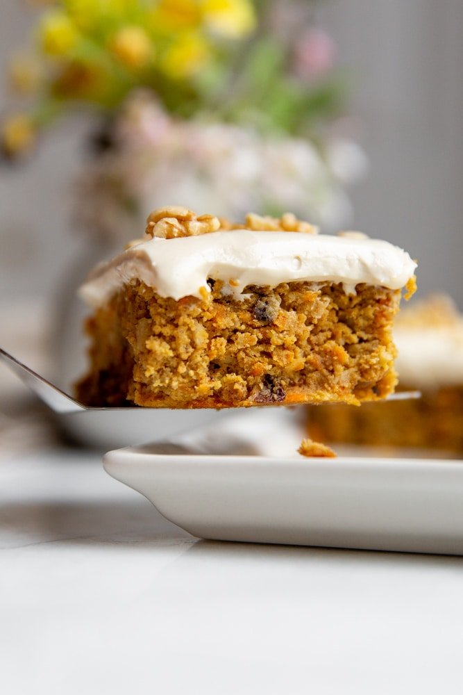 Close up of a piece of gluten free carrot cake with maple cream cheese frosting on a spatula.