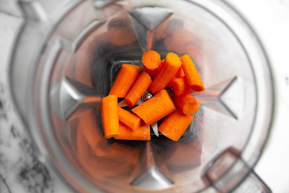 Process shot showing carrots in a Vitamix blender for the carrot cake batter.