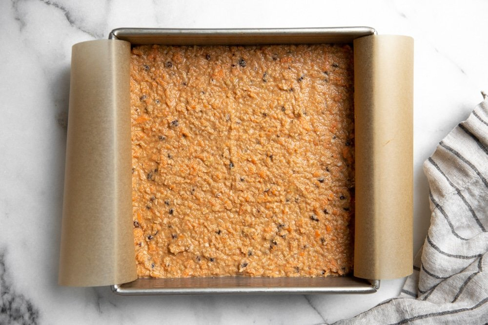Healthy carrot cake batter spread in a cake pan.