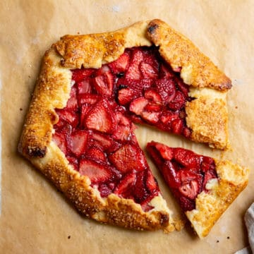 Strawberry galette on a piece of parchment paper with a slice pulled out.