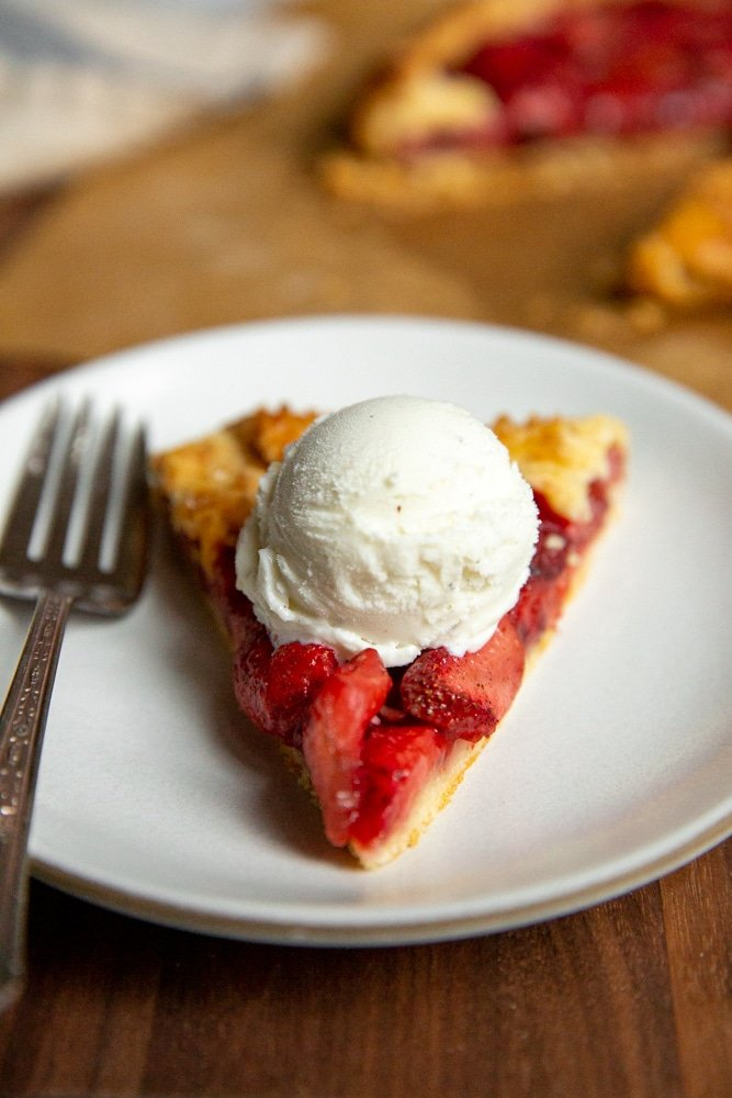 A slice of galette on a plate, topped with a scoop of vanilla ice cream.